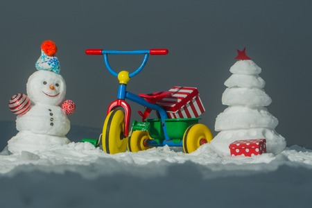 Snowman and snow xmas tree on grey sky. Tricycle with present box on snowy background. Christmas and new year celebration. Festive surprise and gifts. Winter holidays concept Stock Photo