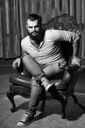 One stylish fashionable handsome brunette man with long lush beautiful beard in grey shirt and blue jeans sitting on brown leather retro chair looking forward indoor on studio background, vertical pic 版權商用圖片