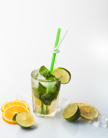 Cocktail isolated on white background. Drink and food. Alcoholic mojito beverage and lime at restaurant. Fruit slice and cocktail glass at bar. Party and summer vacation. Stock Photo
