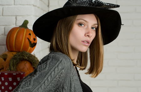 Halloween pumpkins, present box and wreath on white brick wall. Girl posing in witch hat. Woman with red hair and no makeup on face. Holiday celebration concept. Tradition and traditional symbols.