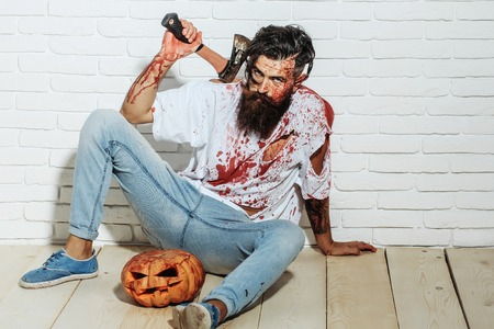 Halloween bearded zombie man, long beard, brutal caucasian hipster with moustache with serious face in red bloody shirt holds pumpkin, axe with wounds and red blood on white brick wall background
