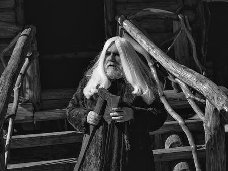 長い銀色の髪とひげログ家背景の上に斧を持つ毛皮コート スタンドで古い人間ドルイド
