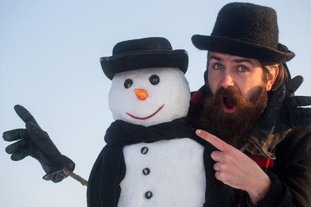 Man and snowman pointing fingers. Gentlemen in black hats and scarves on blue sky. Surprised hipster with open mouth. Winter holidays celebration. Christmas and new year concept. Stock Photo