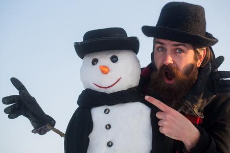 Man en sneeuwman wijzende vingers. Heren in zwarte hoeden en sjaals op blauwe hemel. Verbaasd hipster met open mond. Wintervakanties. Kerstmis en Nieuwjaar concept.
