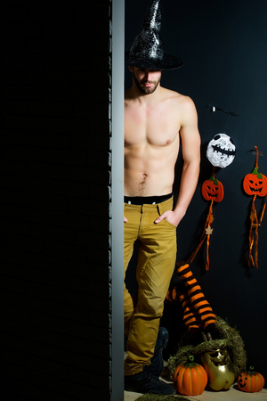Halloween autumn holidays celebration. Spirit and supernatural concept. Macho standing in witch hat and bared torso. Man and pumpkins, stockings, ghost on black wall. Evil spell and magic, copy space