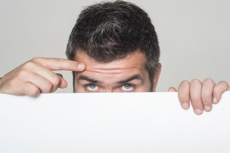 Guy on grey background. Feeling and emotions. Hipster hide face behind white paper. Man with stylish hair.