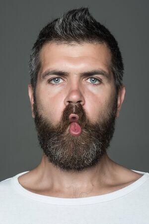 灰色の背景に感情的な顔をしかめる顔が長いひげを持つ男