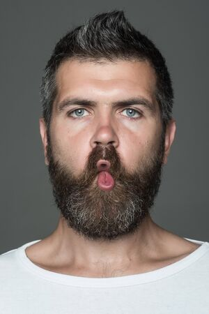 man with long beard on emotional grimace face on grey background