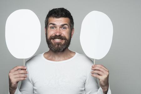 長いひげと口ひげを持つ男。幸せそうな顔で流行に敏感な紙の銘板を保持します。男や背景が灰色のひげを生やした男。感覚や感情。理容ファッシ 写真素材