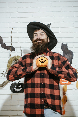 Halloween man smiling pumpkin in witch hat. Happy hipster with beard in plaid shirt. Holiday celebration symbols on grey brick wall. Mystery and horror concept. Trick or treat.