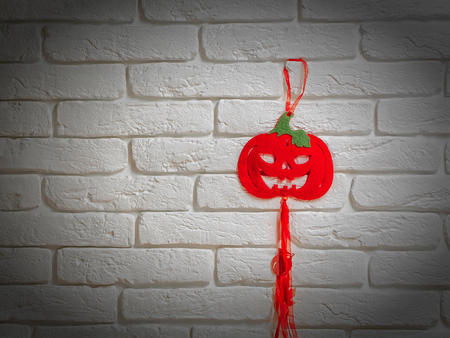 Halloween red pumpkin symbol decoration hanging on white brick wall. Holidays celebration concept, copy space