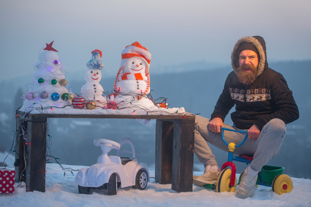 Excited man riding tricycle on snow. Bearded hipster shouting in coat with hood. Snowmen and snowy xmas tree on wooden table. Christmas and new year presents. Winter holidays celebration concept.