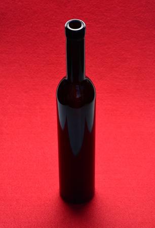 빨간색 배경에 유리 와인 병
