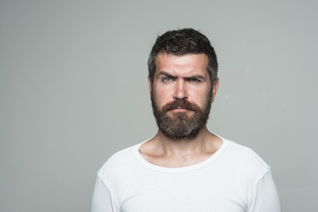 Hipster with serious face. Feeling and emotions. Guy or bearded man on grey background. Barber fashion and beauty. Man with long beard and mustache., copy space Stok Fotoğraf