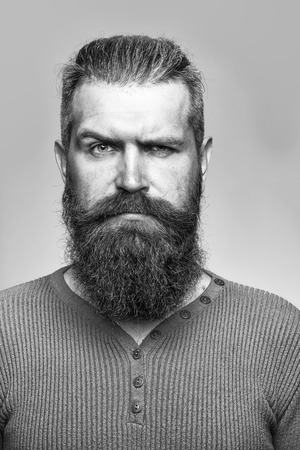 긴 무성 한 수염과 회색 배경에 studio에서 노란색 셔츠에 심각한 얼굴에 콧수염 잘 생긴 수염 난된 남자