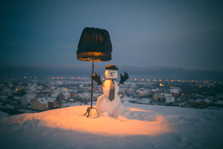 Christmas or xmas decoration. Snowman gentleman with black lamp. Happy holiday and celebration. New year snowman from snow in hat, gloves and tie. Winter evening party. 스톡 콘텐츠