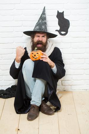 Hipster halloween con calabaza y gato negro símbolo en la cara . hombre en el sombrero de bruja de miedo con gesto ganador en mal estado mal concepto . deseo malo y navidad wow vacaciones . Foto de archivo - 86956725