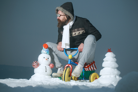 Christmas and new year fun. Man riding tricycle on grey sky. Snowman and snow xmas tree on winter landscape. Hipster in pilot glasses and hood on bike. Holiday celebration concept.