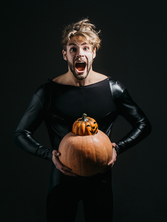 Halloween macho holding two pumpkins on dark background. Scared man shouting in black costume. Autumn and harvest season. Holidays celebration concept. Trick or treat.