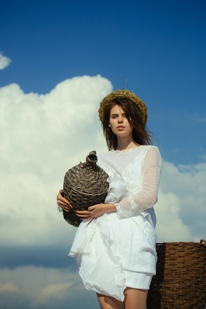 Woman in white dress and wreath on cloudy sky. Summer vacation, holidays and celebration. Harvesting and winemaking. Winery tour concept. Girl with wicker bottle and harvest basket. Фото со стока