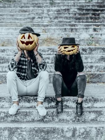 キャップのハロウィーン カボチャ男。流行に敏感なカップルが灰色の階段に座っています。帽子のカボチャの女性。ハロウィーン ジャック o ランタ 写真素材