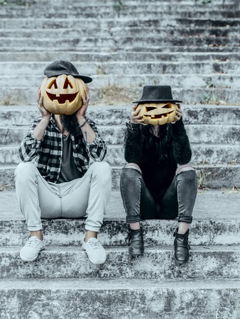 Halloween pumpkin man in cap. Hipster couple sitting on grey stairs. Pumpkin woman in hat. Halloween jack o lantern symbols. Holiday celebration concept.