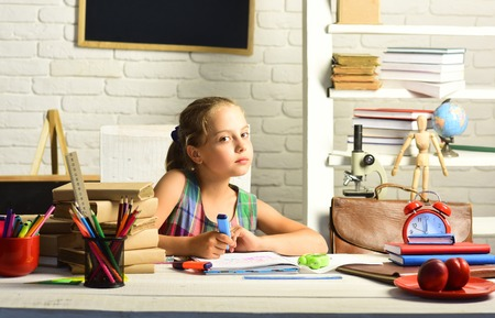 Pupil with books and school supplies. Kid with colorful stationery on white wall background. Childhood and back to school concept. Girl with serious face does homework.