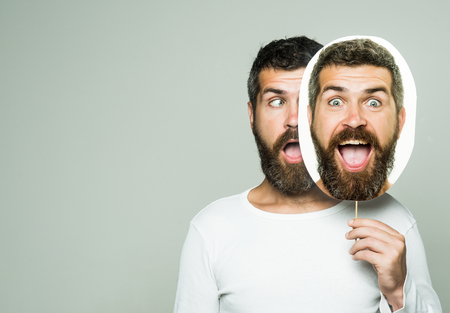Hipster with surprised face hold portrait nameplate. Feeling and emotions. Guy or bearded man on grey background. Barber fashion and beauty. Man with long beard and mustache., copy space