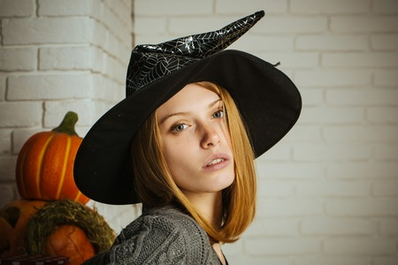 Halloween woman in witch hat. Girl with red hair and no makeup on face. Pumpkins and straw wreath on white brick wall. Holiday celebration concept. Tradition and traditional symbols.