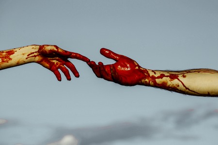 Halloween vampires touching fingers on grey sky background. Two female and male hands connecting. Skin with red blood and bloody wounds. Connection and support. Halloween holiday celebration concept.