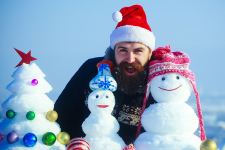 Santa man smiling with snowy sculptures. Happy hipster in santa claus cap on winter day. Snowmen in hats and snow xmas tree on blue sky. Christmas and new year. Holidays celebration concept