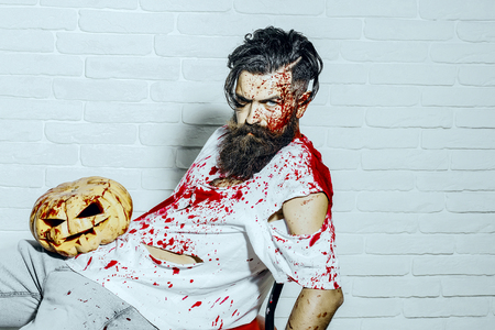 Halloween war soldier bleeding in torn tshirt. Man sitting with pumpkin on white brick wall. Maniac and bloody jack o lantern. Bearded hipster with red blood splatters. Halloween holiday concept.