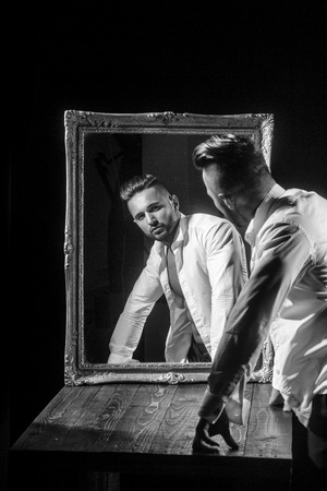 handsome muscular macho man or athlete guy with sexy body of bodybuilder, has beard on serious face in white shirt near vintage mirror isolated on black background