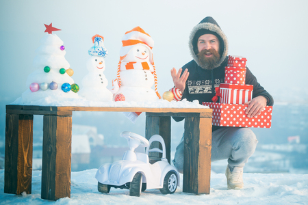 Happy hipster holding present boxes. Bearded man smiling with gifts on blue sky. Toy car under table with snowmen and xmas tree. Christmas and new year celebration. Winter holidays concept. Stock Photo