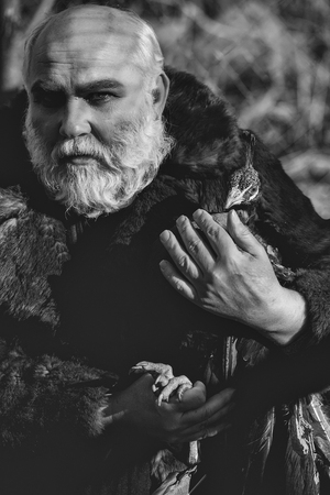 old bearded man with long white beard on serious face with makeup in fur coat holding colorful peacock bird sunny day outdoor Stock Photo