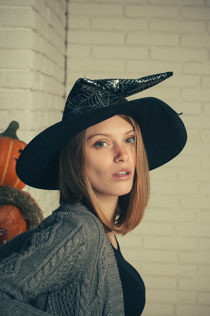 Halloween girl in witch hat. Woman with red hair and no makeup on face. Pumpkins and straw wreath on white brick wall. Holiday celebration concept. Tradition and traditional symbols.
