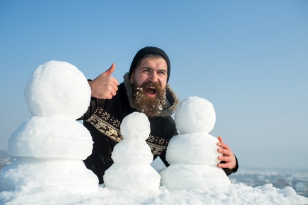 Père Noël hipster en manteau et bonhomme de neige. Mec de nouvel an sur le ciel bleu avec la figure de la neige. Vacances d'hiver et fête de Noël. Bonhomme de neige en neige blanche homme de Noël avec une longue barbe. Banque d'images - 87042716