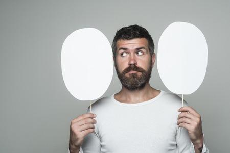 深刻な顔で流行に敏感な紙の銘板を保持します。長いひげと口ひげを持つ男。感覚や感情。男や背景が灰色のひげを生やした男。理容ファッション