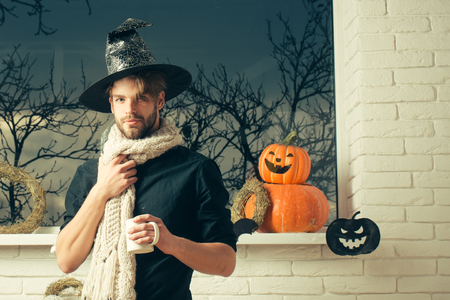 Halloween holiday symbols and decorations. Man holding cup at window with autumn trees. Magic potion concept. Macho wearing witch hat and scarf. Warm and homely atmosphere. Stock Photo