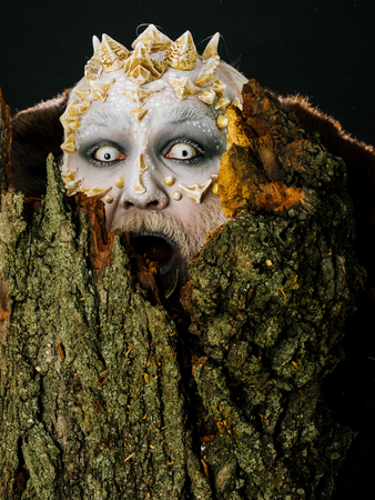 Goblin shouting with horns on head. Monster with sharp thorns and warts. Druid behind old bark on black background. Tree spirit and fantasy concept. Man with dragon skin and scary face.