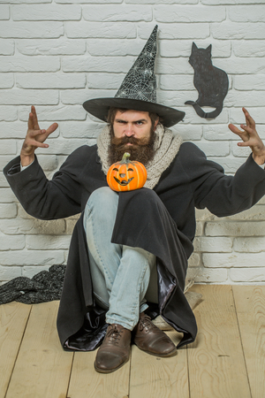 Halloween evil spell. Man in witch hat doing magic on floor. Bad luck concept. Hipster with pumpkin and black cat symbol on wall. Autumn holidays celebration.