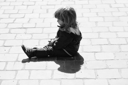 Small boy with blonde hair sitting on paving stones sunny day outdoor
