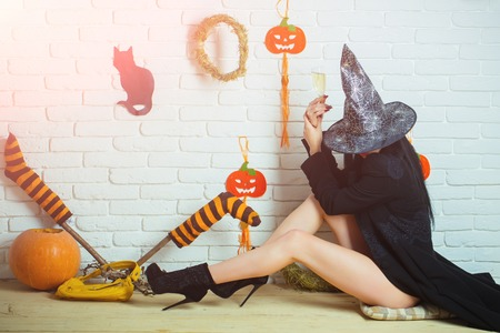 Halloween woman in witch hat and coat sitting on floor. Girl with pumpkins, striped stockings, black cat on wall. Evil spell and magic. Tradition and traditional symbols. Holiday celebration concept. Фото со стока