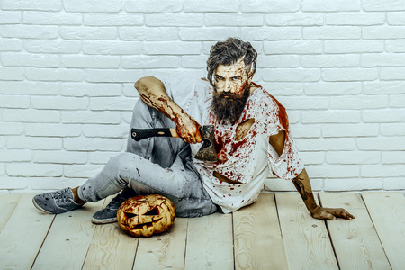 Halloween bearded hipster with red blood splatters. Man sitting with pumpkin and axe on wooden floor. Psychopath bleeding in torn tshirt. Maniac and bloody jack o lantern. Halloween holiday concept.