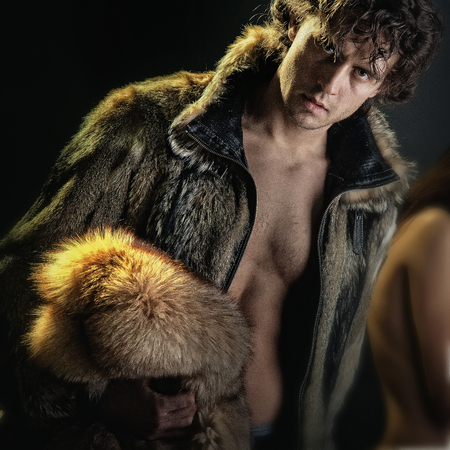 Man or macho posing in open fur coat of brown furry animal hides with bare torso on dark background. Fashion and clothing. Glamour and luxury lifestyle concept