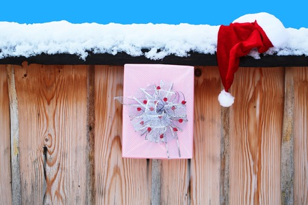 Santa presents on snowy fence isolated on blue. New year and xmas. Winter palisade with white snow. Santa claus hat and Christmas box on wooden background. Holidays celebration concept.
