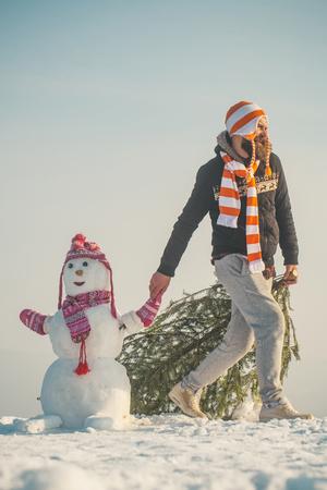 Hipster slepende Kerstmis boom op besneeuwde winter weg. Kerel en sneeuwbeeld die hoeden en sjaals dragen. Mens en sneeuwman die op blauwe hemel lopen. Vakantie feest concept. Kerstmis en Nieuwjaar.