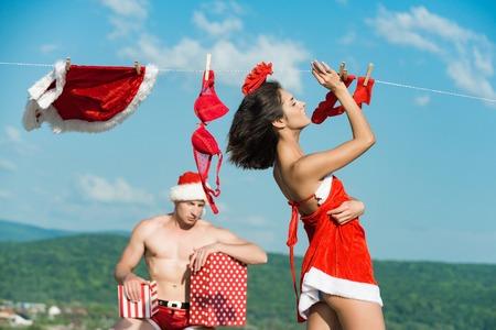 男と乾燥のため洋服をかけられる女の子の愛のカップル。新年に筋肉ボディと青い空の男。クリスマスの男と女の家族。ランドリー、ドライ クリー 写真素材