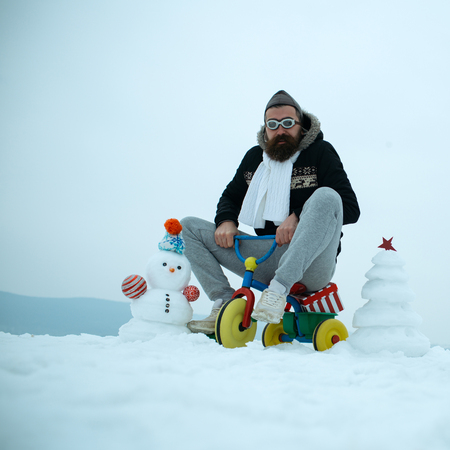 Snowman and snow xmas tree on winter day. Hipster in pilot glasses and hat on bike. Christmas and new year fun. Holiday celebration concept. Man riding tricycle on snowy landscape. Stock Photo