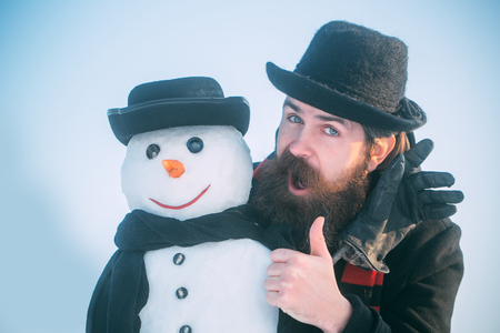 Man or hipster with beard giving thumbs up hand. Snowman with smiley face in gloves. Gentlemen in black hats and scarves on blue sky. Christmas and new year concept. Winter holidays celebration